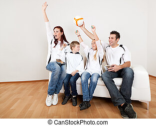 Young family watching football match at home