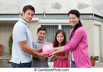 Savings concept - Happy family with piggy bank