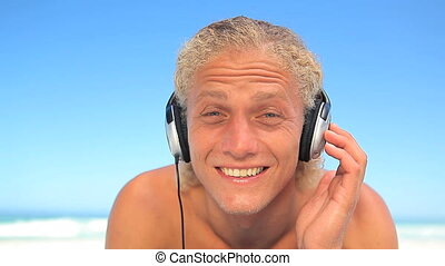 Blonde man listening to music with headphones on the beach