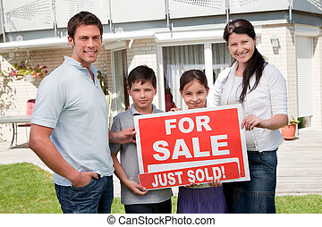 Family with a sale sign outside their new home - Portrait of...