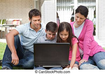 Young family in backyard using laptop