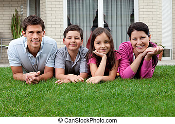 Portrait of happy young family lying on grass outside their...