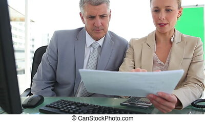 Businessman discussing a document with his colleague in an...