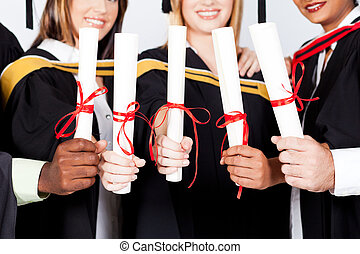 multiracial graduates holding certificates - group of...