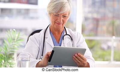 Smiling doctor using a tablet computer in a bright office