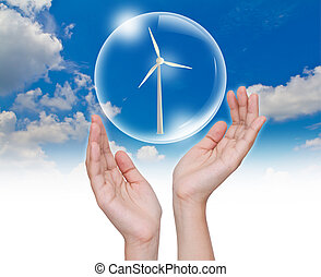 Hand holding bubble with Wind Turbine inside over blue sky