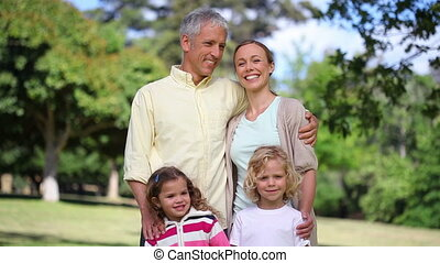 Couple with two children posing in a park