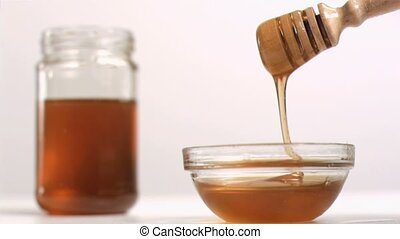 Honey flowing in super slow motion from a spoon in studio