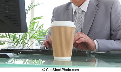 Businessman drinking a cup of coffee while typing