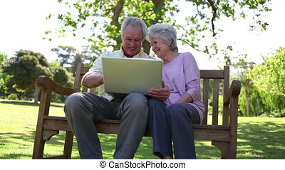 Retired people using a laptop in a park