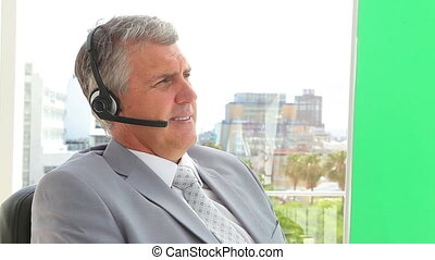 Businessman gesturing while talking on a headset in an...