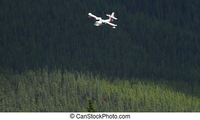 Water Bomber sprays the forest - A water bomber sprays water...