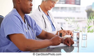 Serious medical people writing on their notepads in a bright...