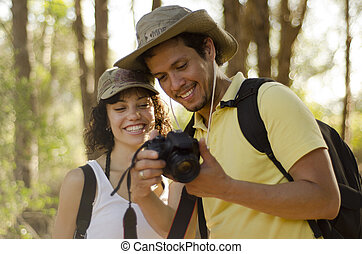 Cute couple looking at their photos - Cute young couple...
