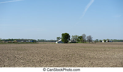 barren farm land and house before the crops begin to grow