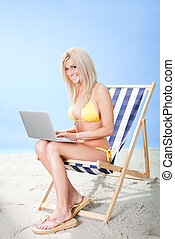 Young woman in bikini using laptop