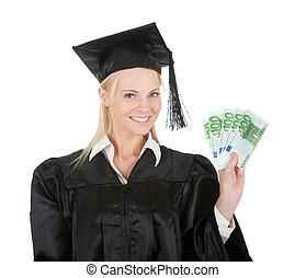 Female graduate student holding money. Isolated on white