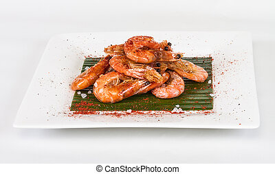 fried black tiger prawns with herbs and spices on banana...