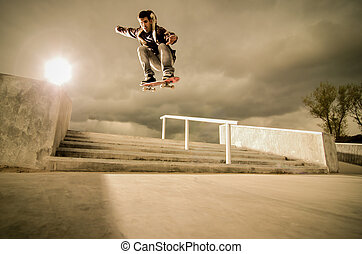 Skateboard ollie - Skateboarder jumping over the stairs on a...