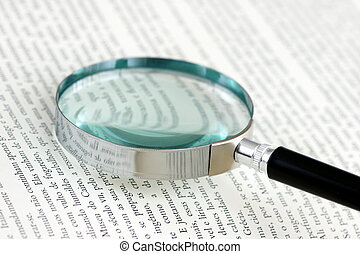 Magnifying glass - A magnifying glass over a page of a book
