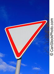 give way - road sign give way on a background of blue sky...