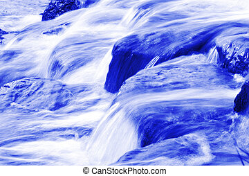Small brooks in blue saturated color mixed with white water...