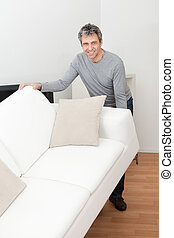 Senior man moving sofa at his home