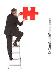 Senior businessman holding a jigsaw puzzle. Isolated in...