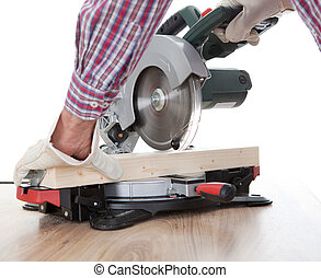 Worker cutting timber using circular saw - Worker cutting...