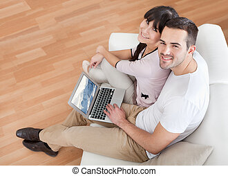 Young couple using laptop in couch - Young couple watching...