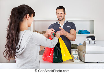 Customer buying clothes in shop - Female customer buying...