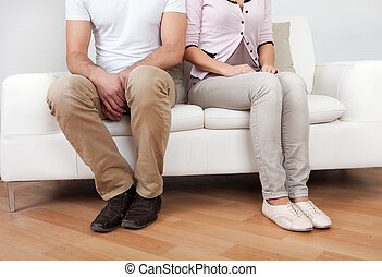 Young couple in quarrel at home Sitting on the couch