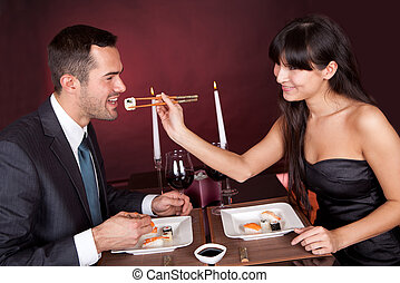 Young couple eating sushi in restaurant