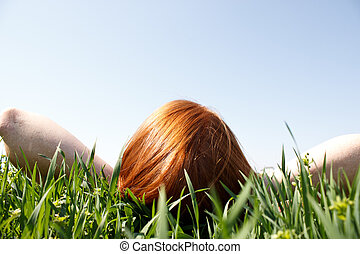 Redhead Laying In Grass Looking Up - Red haired woman laying...