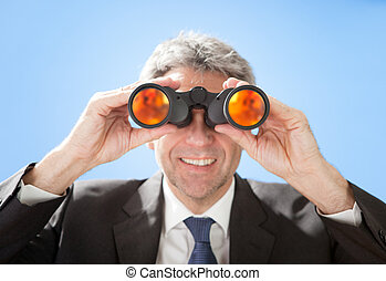 Senior businessman looking through binoculars - Portrait of...