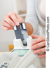 Sales person inserting card into scanner - Sales person...