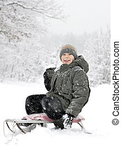 smiling boy with snowball - smiling boy on a sled going to...