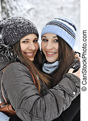 Two young girl wearing warm winter clothes in winter park