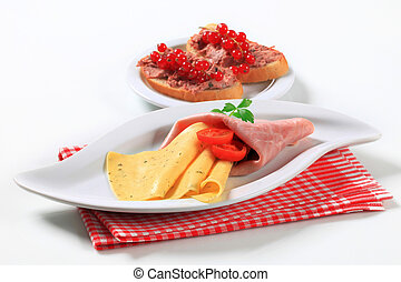 Antipasto - Slices of ham and cheese and bread with pate