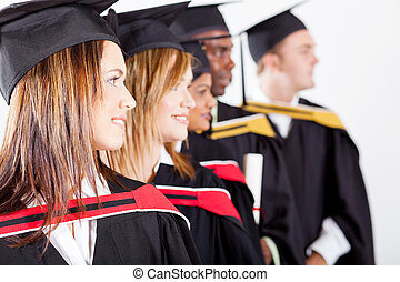 graduates looking away at graduation - group of graduates...