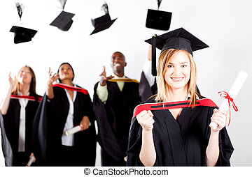 happy female graduate at graduation with classmates throwing...