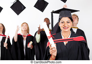 happy female Indian graduate at graduation with classmates...
