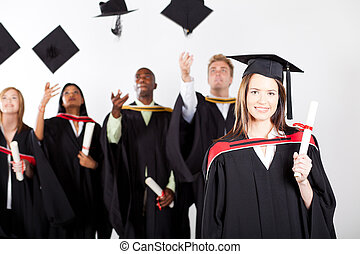 university graduate at graduation with classmates throwing...