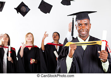 happy African graduate at graduation with classmates in...