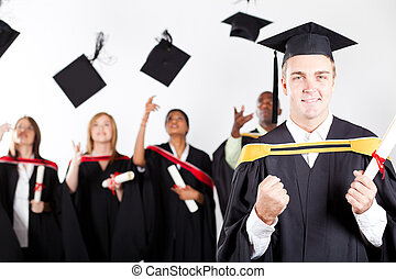 young male graduate at graduation with classmates in...
