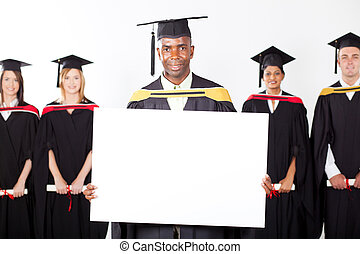 male African graduate with white board in front of...