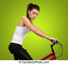 portrait of young woman cycling over green background