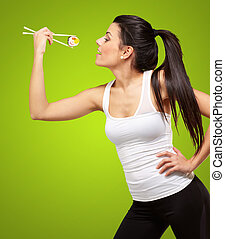 young pretty woman eating sushi over green background