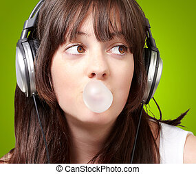 portrait of young woman listening to music with bubble gum over green