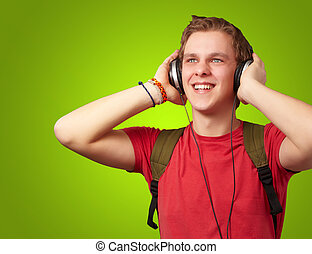 portrait of cheerful young student listening music with headphones over green